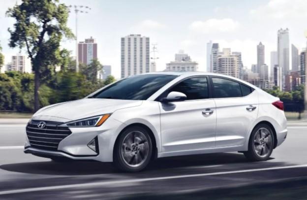 White 2020 Hyundai Elantra cruises down a city street.