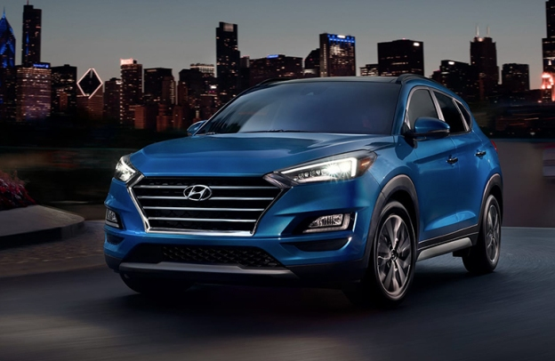 Blue 2020 Hyundai Tucson in front of a city skyline at night.