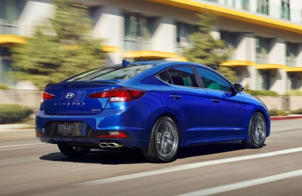 Blue 2020 Hyundai Elantra zooms up a city street in the sun.