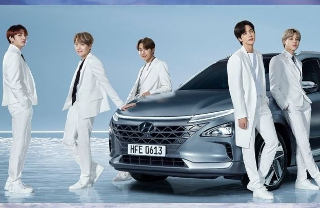 Five of the seven members of BTS lounge around a Hyundai vehicle on a watery surface