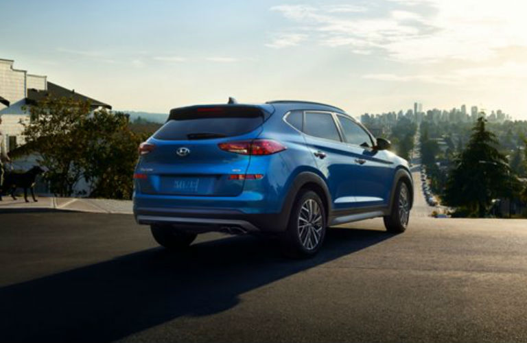 Read/side angled view of 2021 Hyundai Tucson gazing on a city from afar