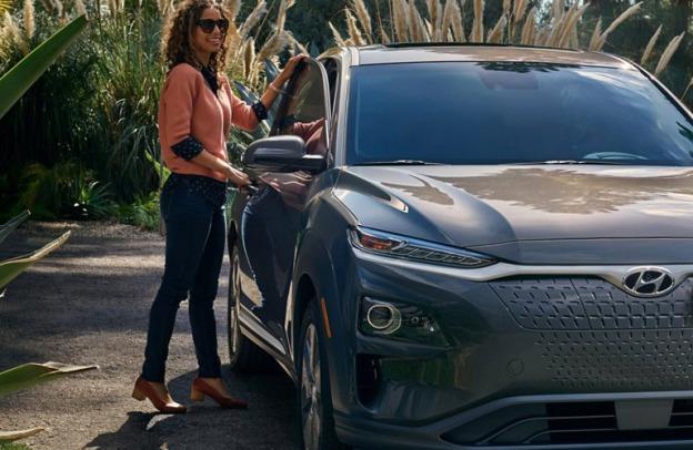 Woman opens door of 2021 Hyundai Kona Electric
